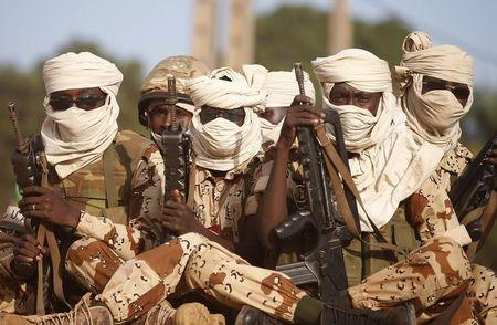 Chadian soldiers sit with guns on a vehicle as they drive in Bangui