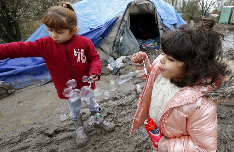 Young migrants make soap bubbles in a muddy field at a camp of makeshift shelters called the Grande Synthe jungle, near Calais