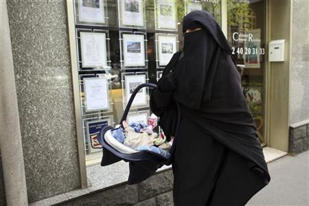 Anne, an assumed name, a 31-year old French woman who has been fined for wearing a niqab while driving, leaves after a news conference in Nantes